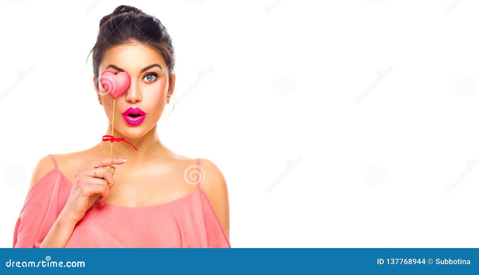 Rosa vermelha Menina nova alegre do modelo de forma da beleza com a cookie dada forma coração do Valentim em sua mão