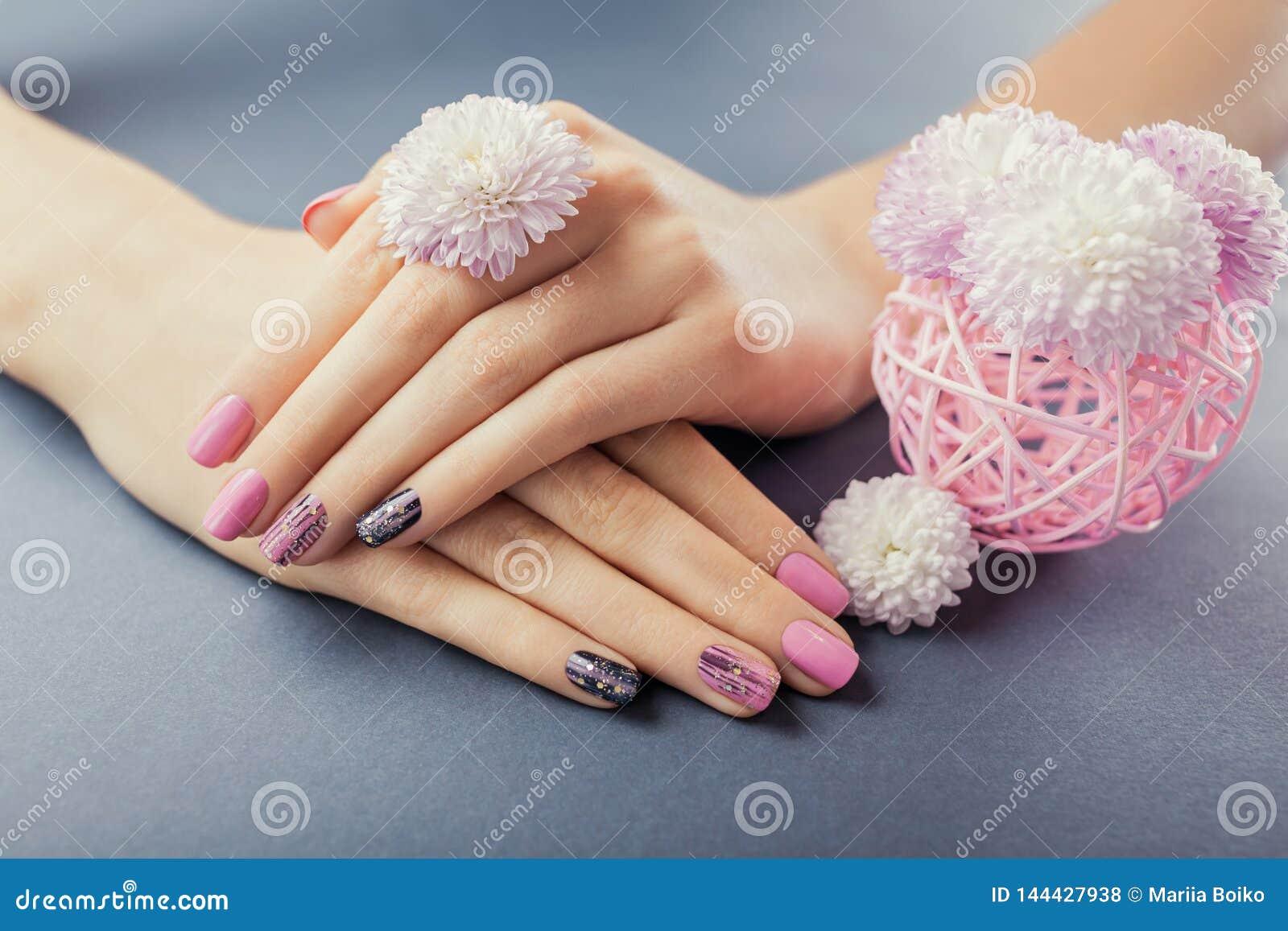 Rosa y manicura negra en las manos femeninas con las flores en fondo gris Arte y dise?o del clavo