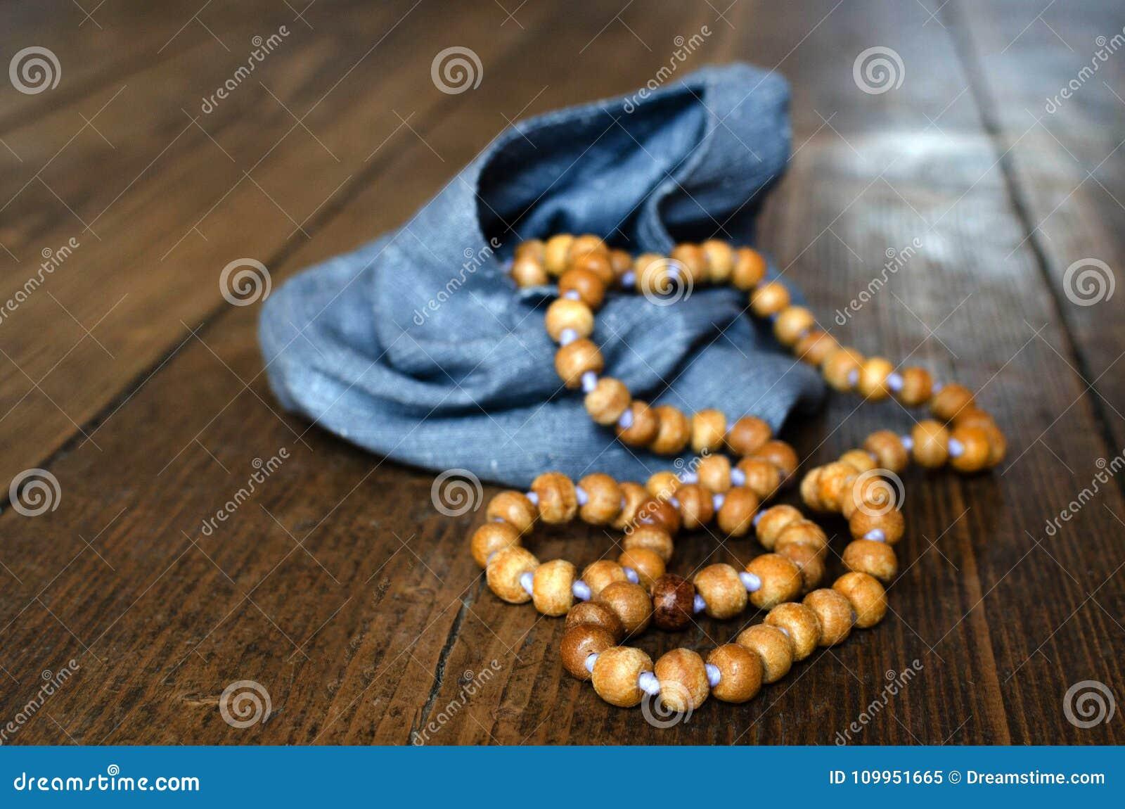 Rosario di legno Rosario di legno in una borsa blu su un pavimento di legno