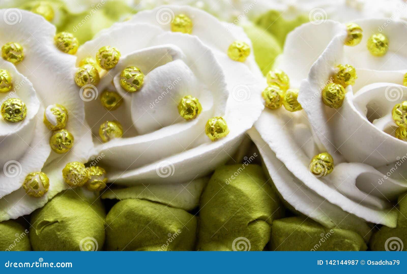 Rosas blancas y hojas verdes hechas con la crema, primer