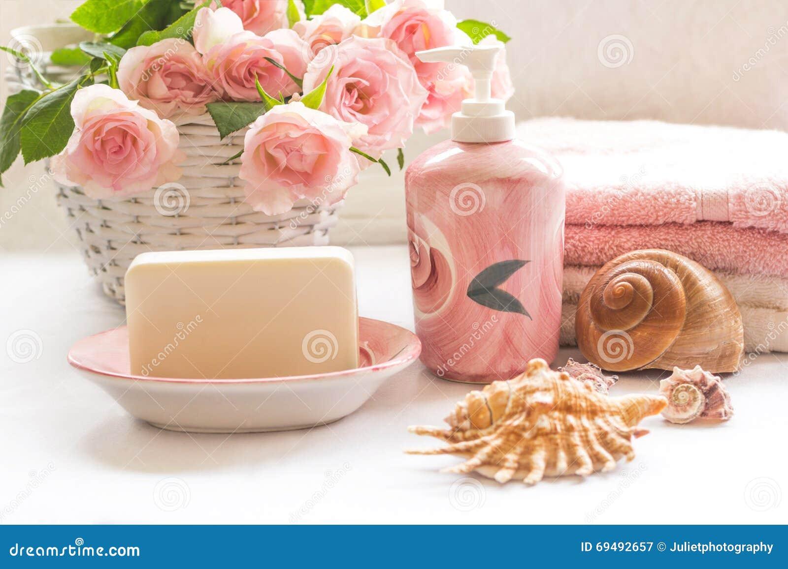 Rosas, jabón, toallas y arreglo rosados de las conchas marinas