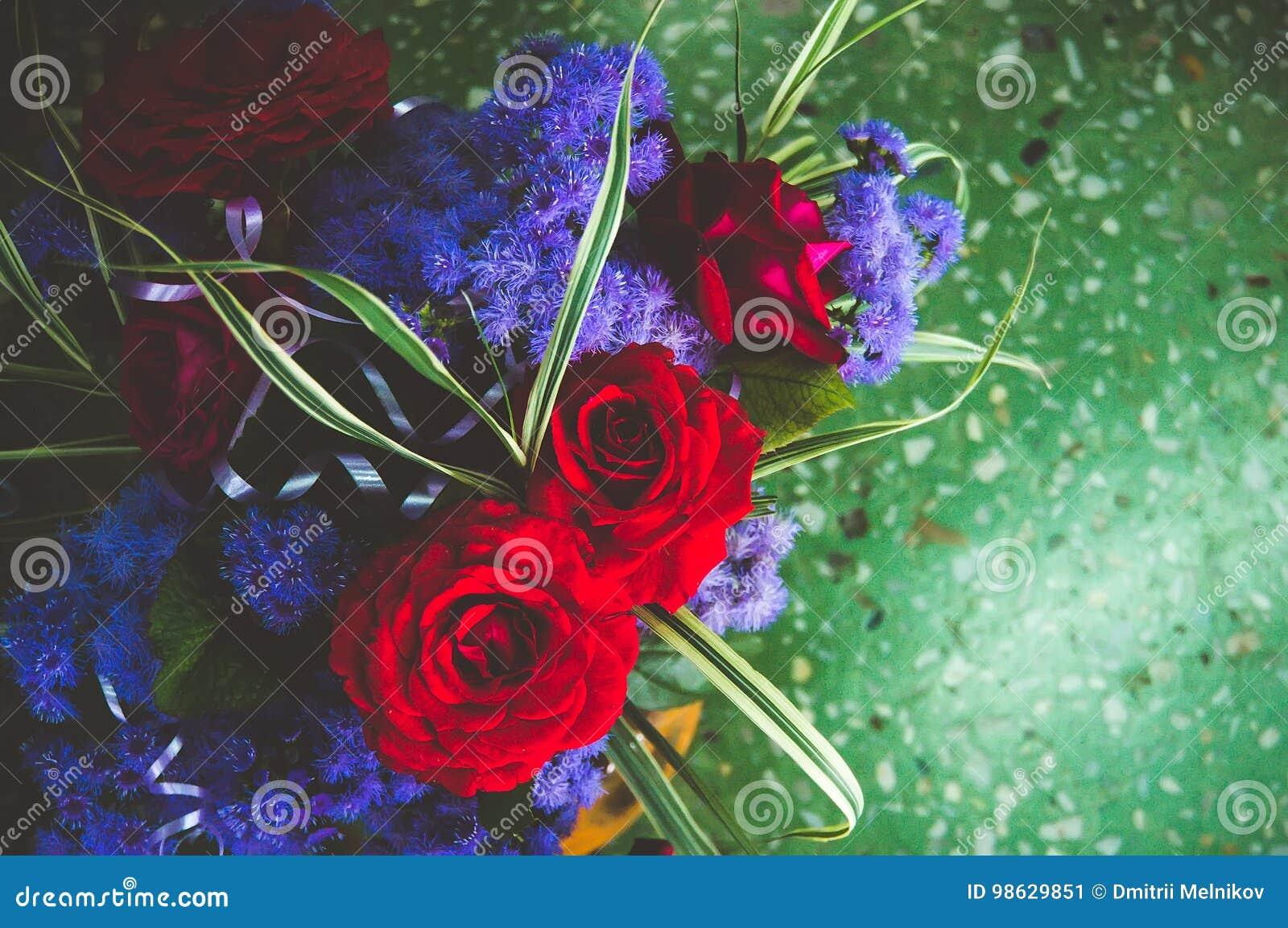 Rosas Rojas Con Las Flores Azules En El Ramo En El Fondo Del Mármol