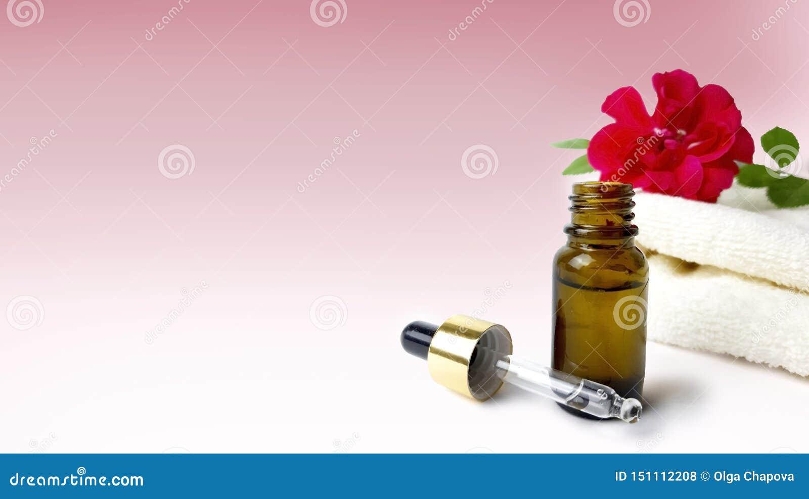 Rosas, toalla, botella de aceite esencial en fondo rosado
