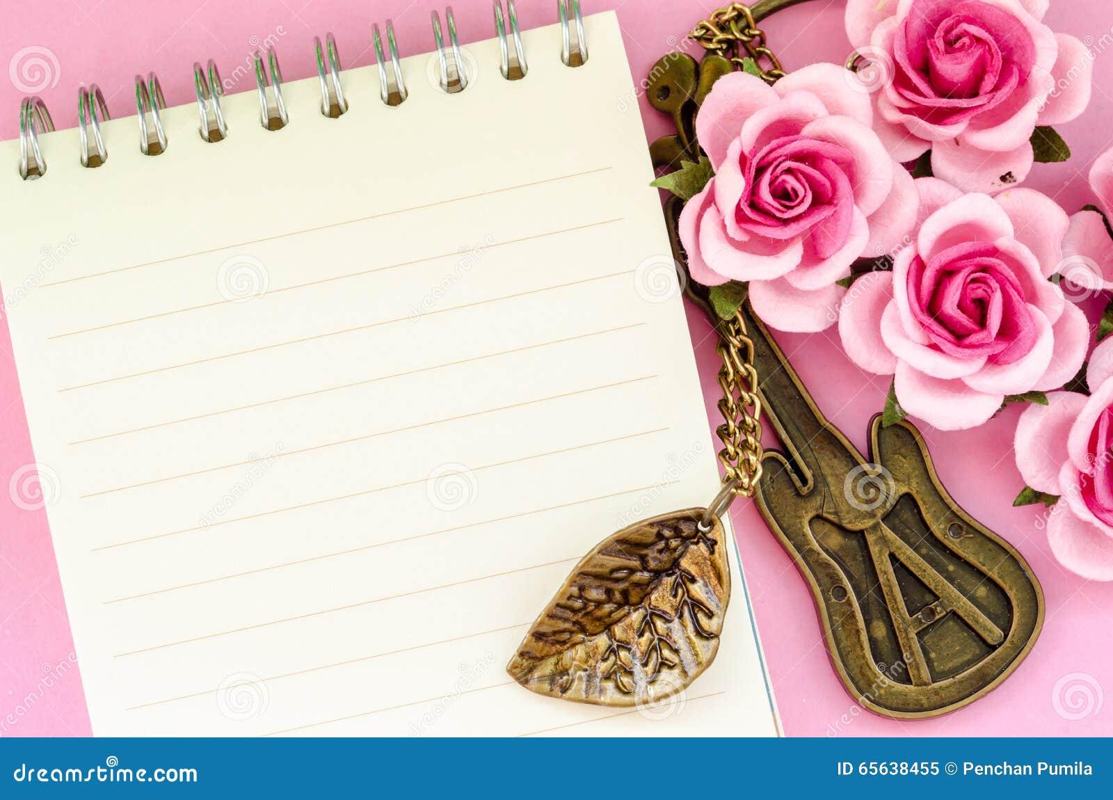 Rose de rose et carnet ouvert sur le fond rose