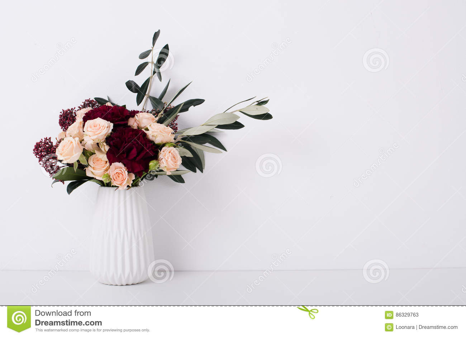 Rose e garofani in un vaso nell interno bianco