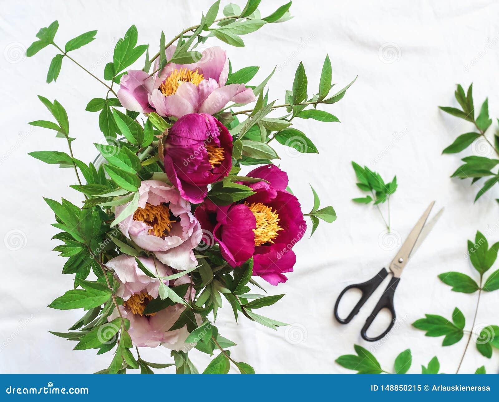 Rose et pivoines pourpres dans un vase sur une table blanche