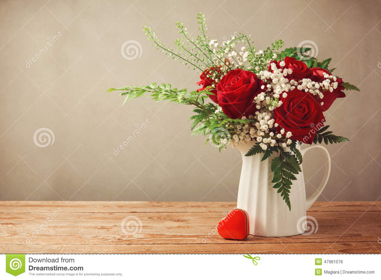 Rose flower bouquet and heart shape box on wooden table with copy space