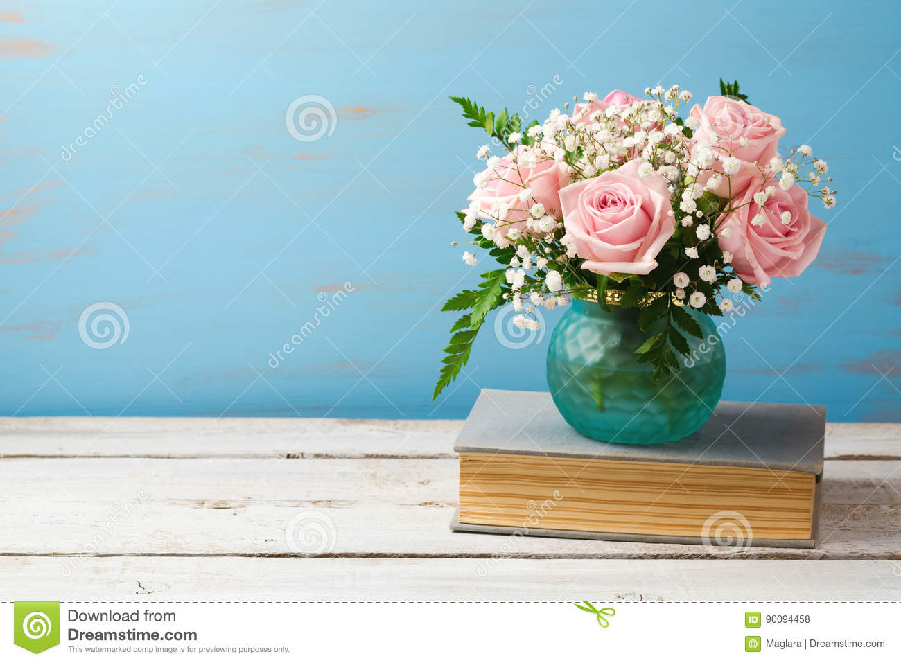 Rose flower bouquet in vase on old books over wooden background