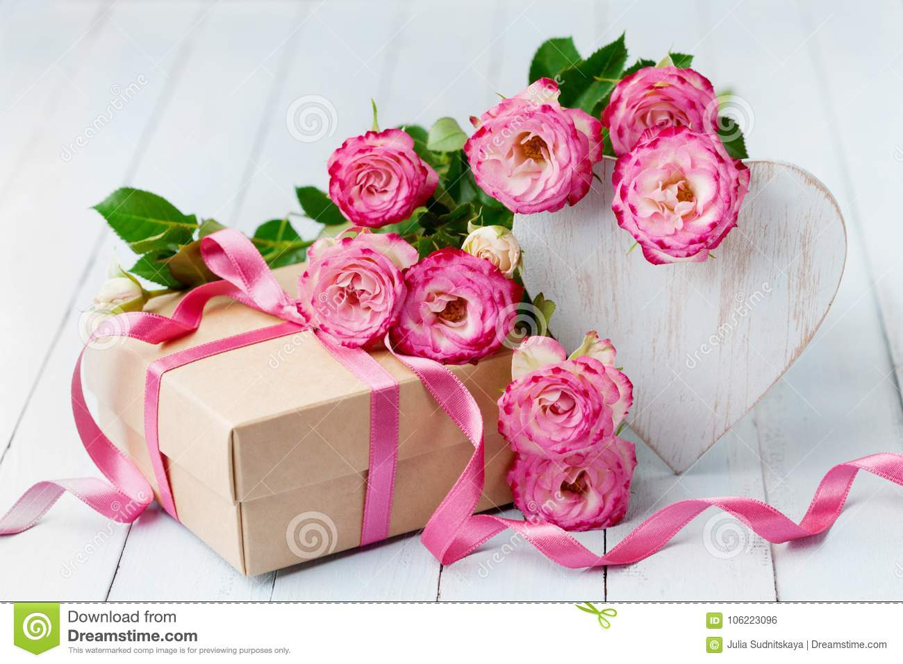 Rose flowers, wooden heart and gift box on blue rustic table. Beautiful greeting card for Birthday, Woman or Mothers Day.