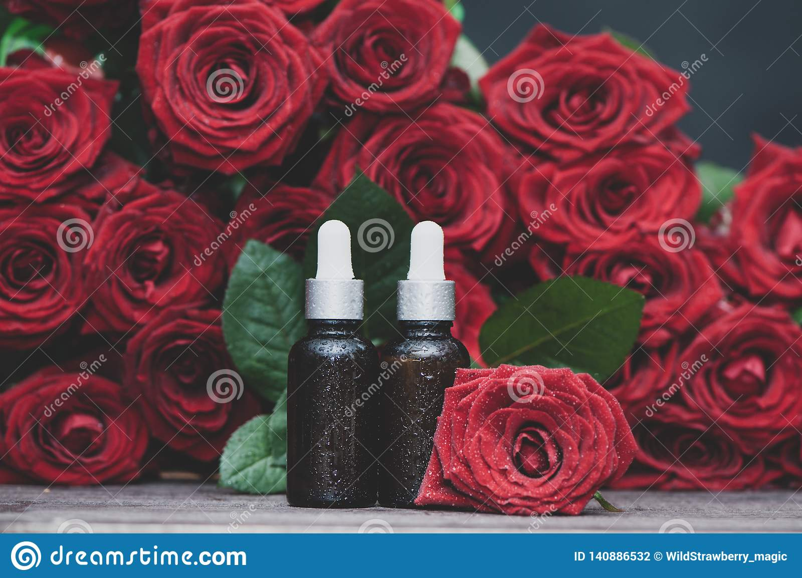 Rose oil, Bottles and fresh flower and leaves on a natural background, bio, organic , nature cosmetics