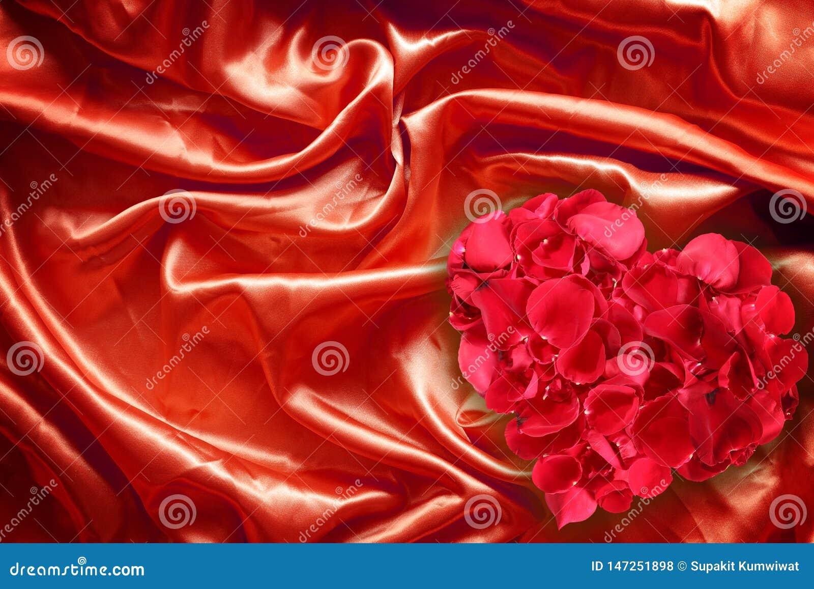 Rose petals on red fabric silk