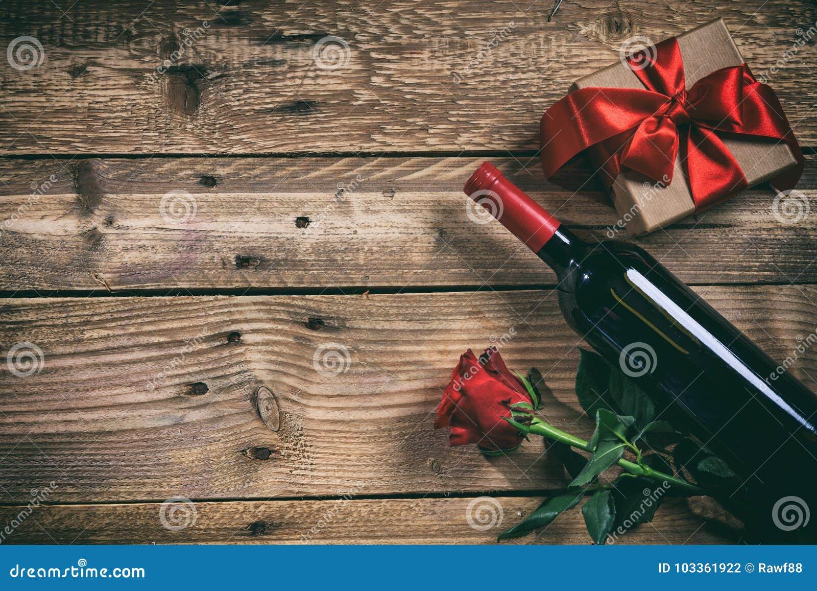 Rose roja Botella de vino rojo, color de rosa y un regalo en fondo de madera