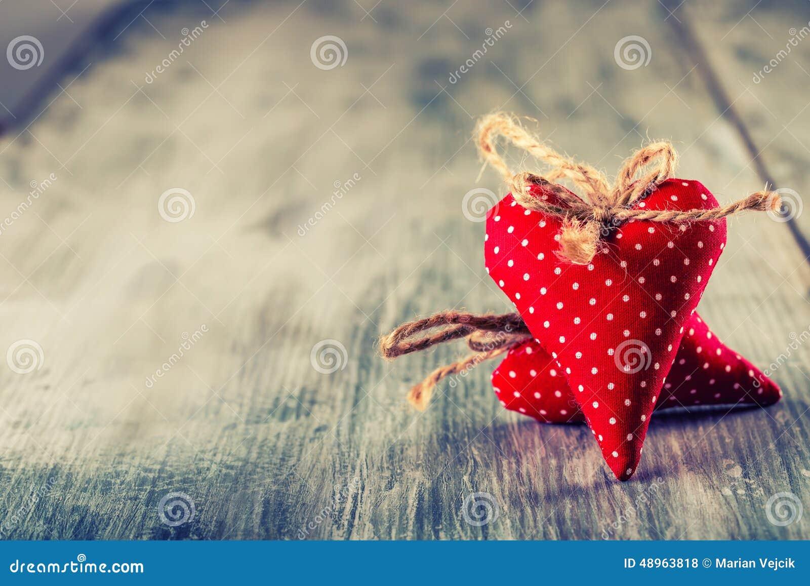 Rose roja Corazones hechos a mano del paño rojo en fondo de madera