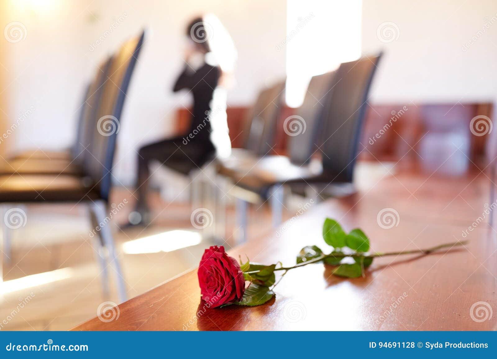Rose rosse e donna che gridano al funerale in chiesa