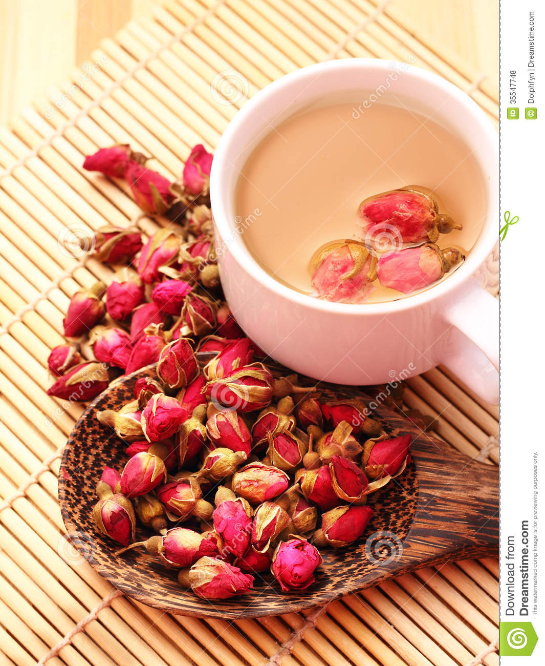 Dried roses, wooden scoop and a cup of rose tea on bamboo mat.