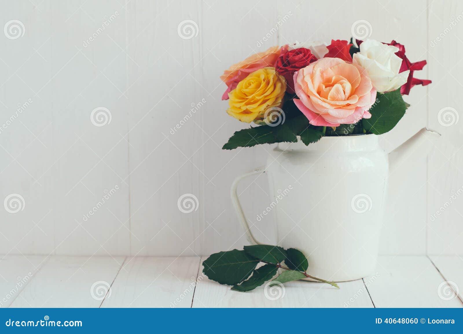 Rose variopinte in caffettiera bianca dello smalto