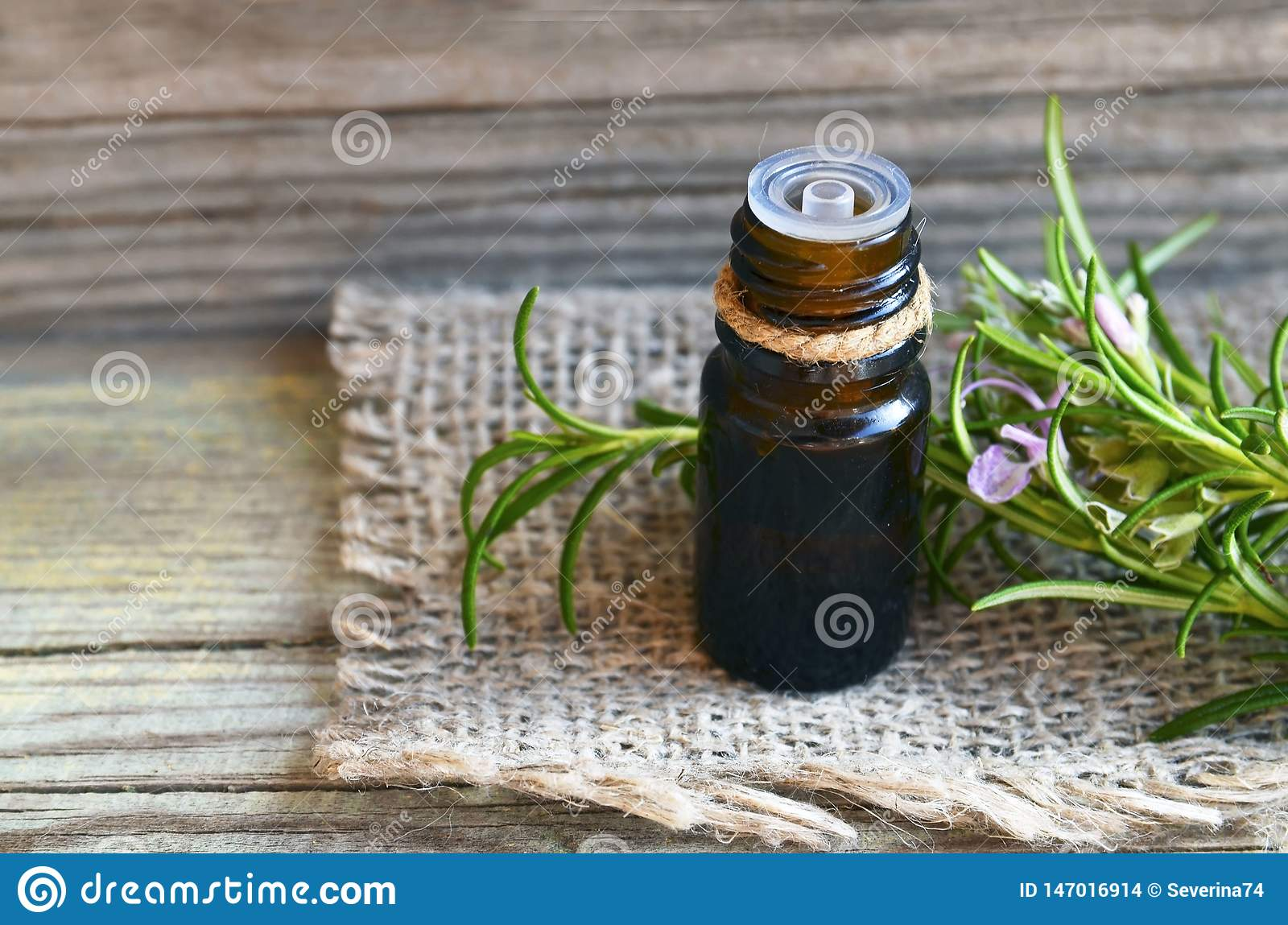Rosemary essential oil in a glass dropper bottle with fresh green rosemary herb on old wooden table for spa,aromatherapy and body