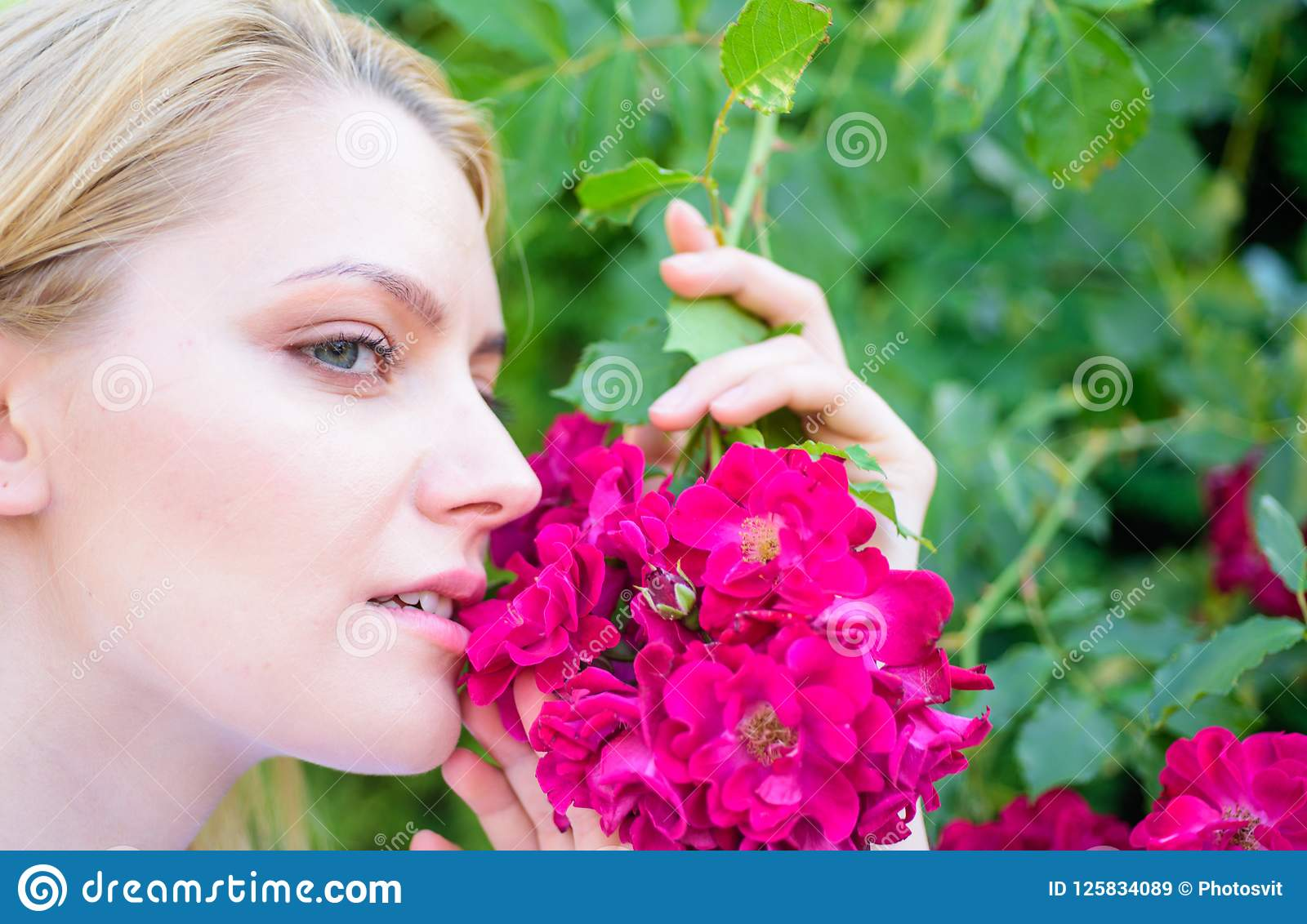 Rosen-Auszugöl-Aromaprodukt Mädchen und Blumen auf Naturhintergrund Schöne Blüte Frauenatemzug blüht Duft