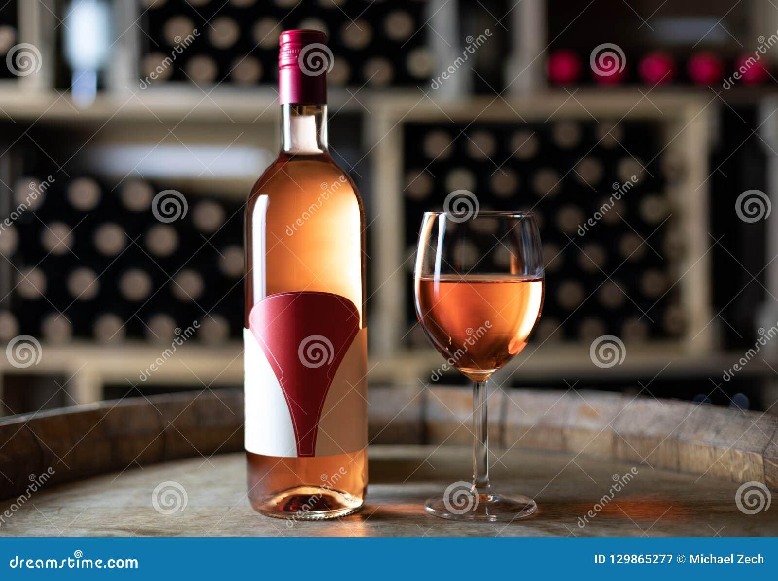 Rosen-Weinflasche mit einem gefüllten Weinglas auf einem Fass in einem Keller