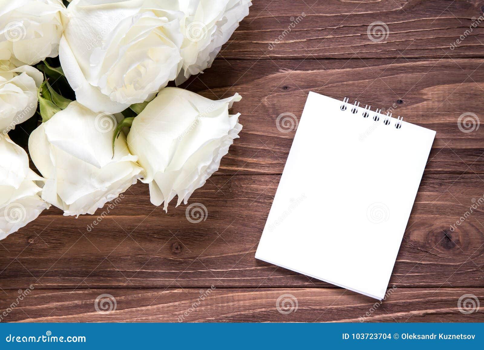 Roses blanches avec le livre blanc vide sur la table en bois