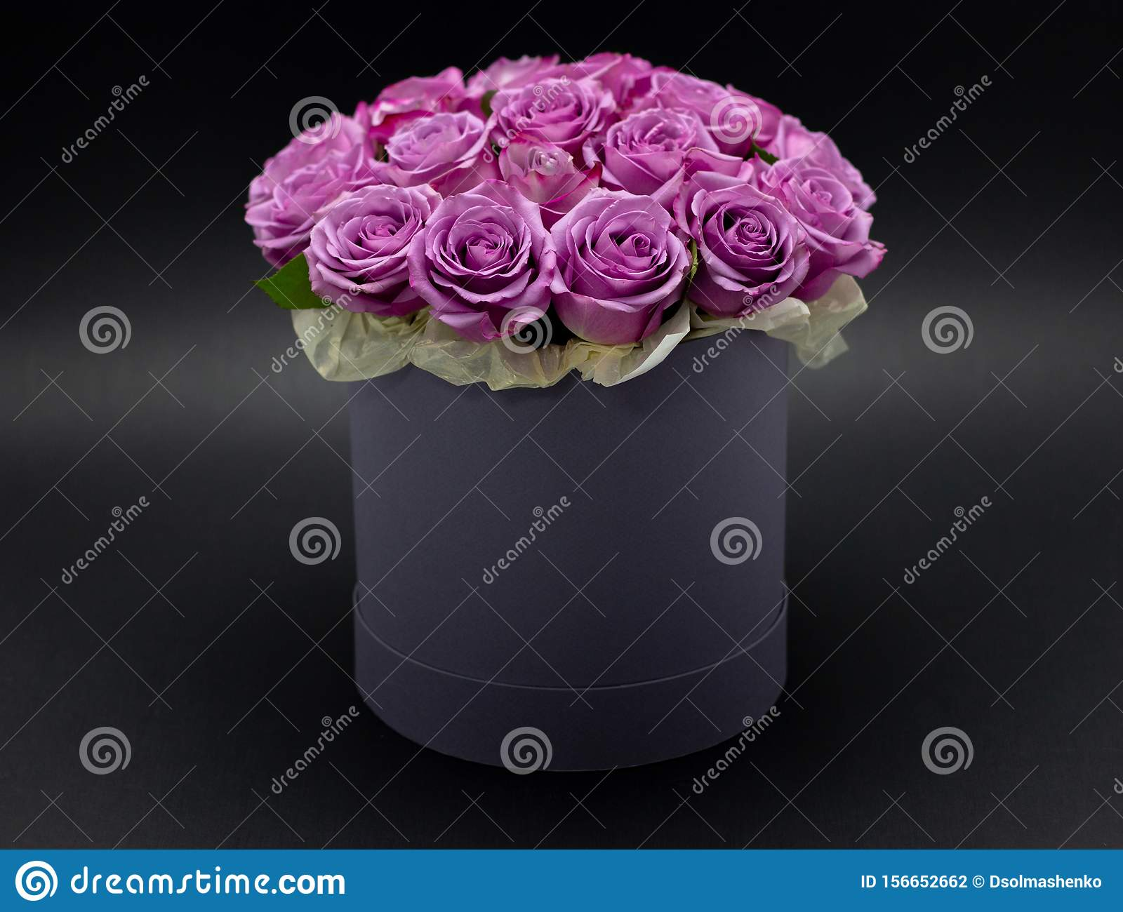 Roses in a hat box on a dark background isolated