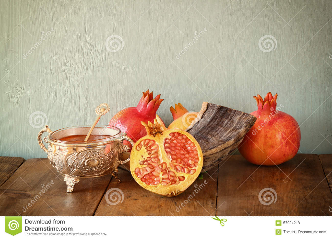 Rosh hashanah (jewesh holiday) concept - shofar, honey, apple and pomegranate over wooden table. traditional holiday symbols.