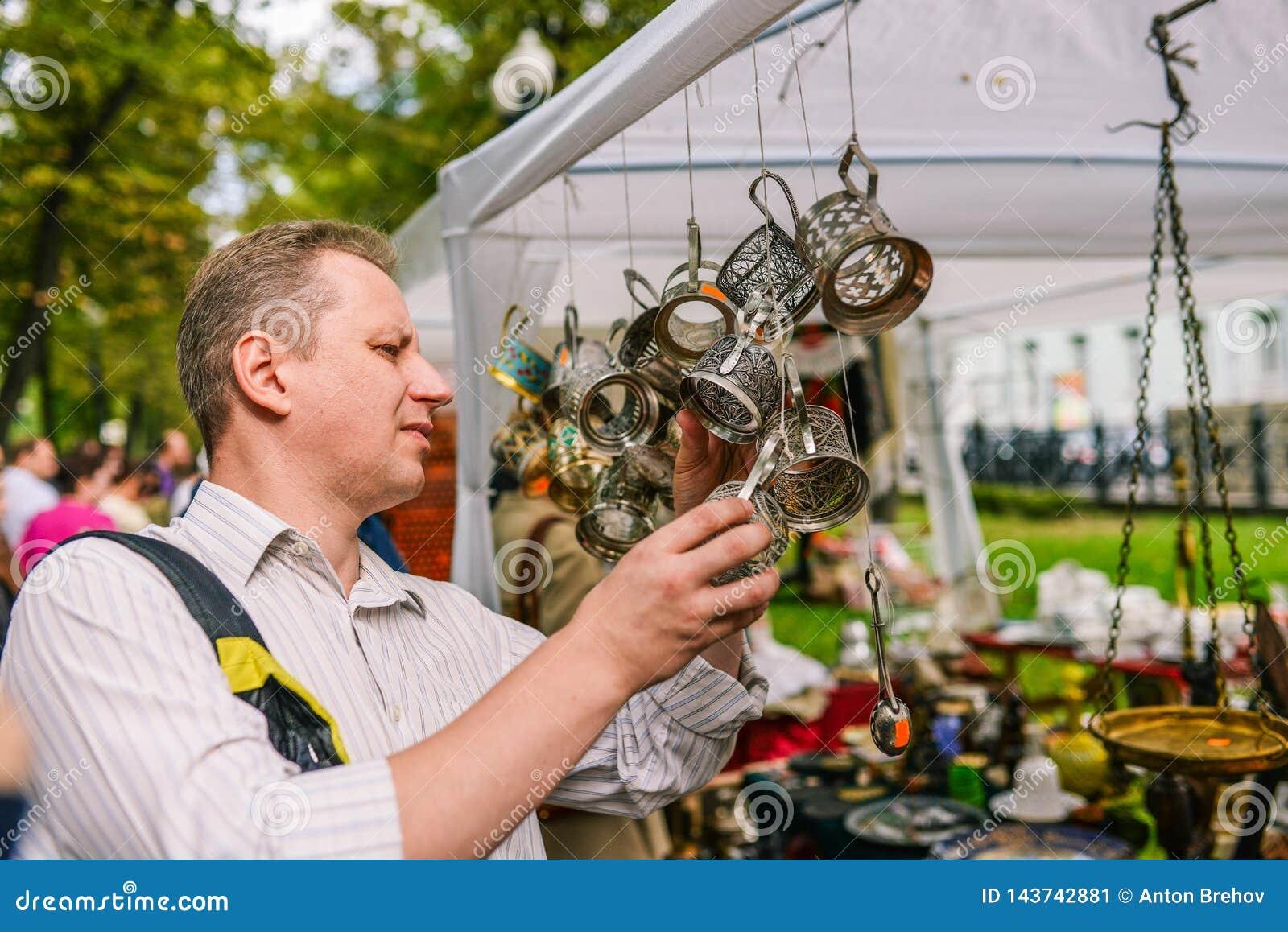Rosja, miasto Moskwa, Wrzesień - 6, 2014: Mężczyzna wybiera kabotażowów Sprzedaż antyki na ulicie Zamiany spotkanie