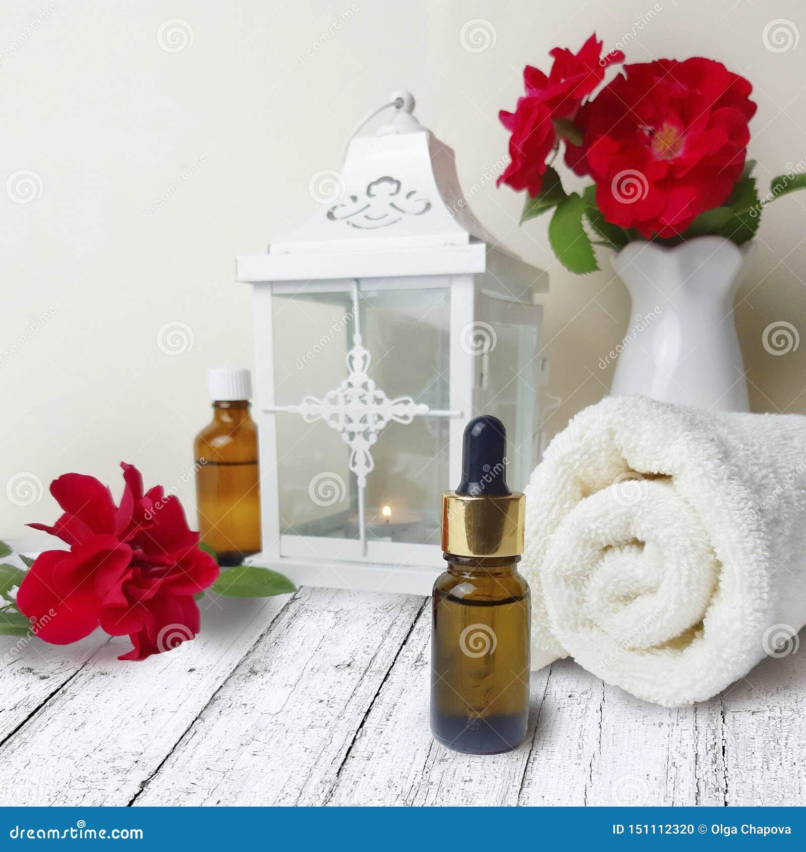 Rosor handduken, lyktan som är nödvändig oljer flaskan på trätabellen