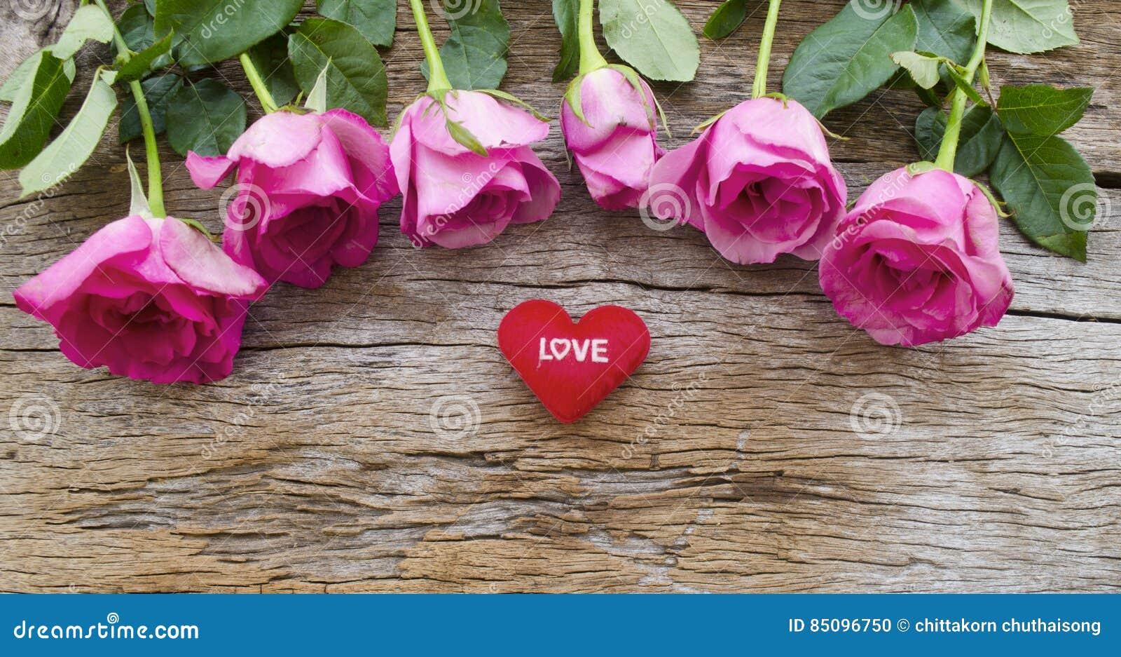 Rosor och röd hjärta kudde på det gamla träbrädet, valentindag b