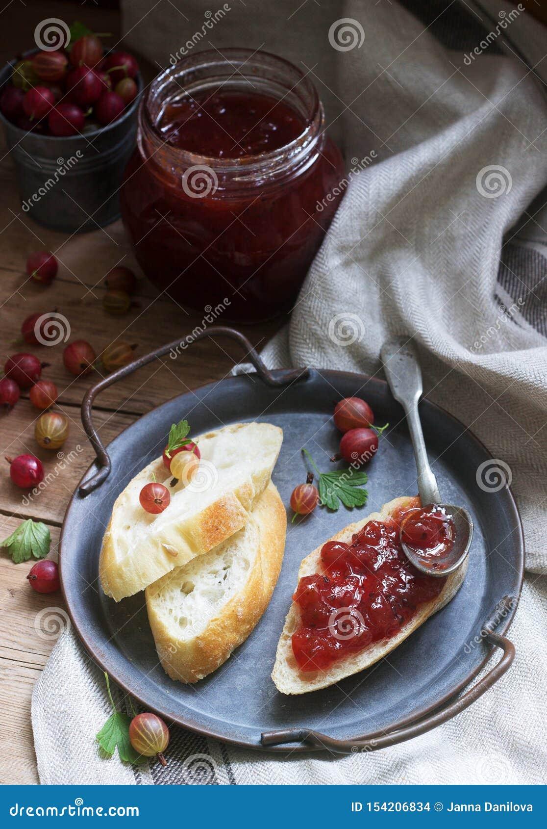 Rostade bröd med krusbärdriftstopp och krusbär på ett tennmagasin Lantlig stil