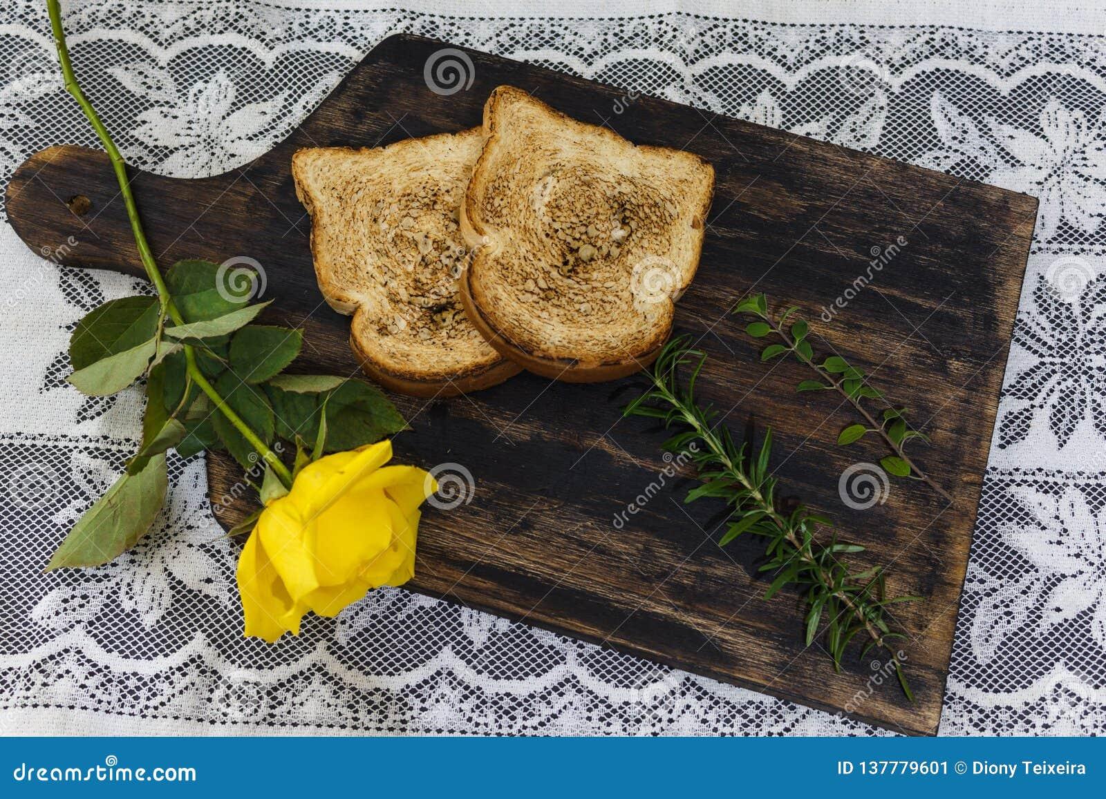 Rostat bröd och rosor, romantisk frukost på Valentine& x27; s-dag Tjänat som på ett träbräde med kopieringsutrymme