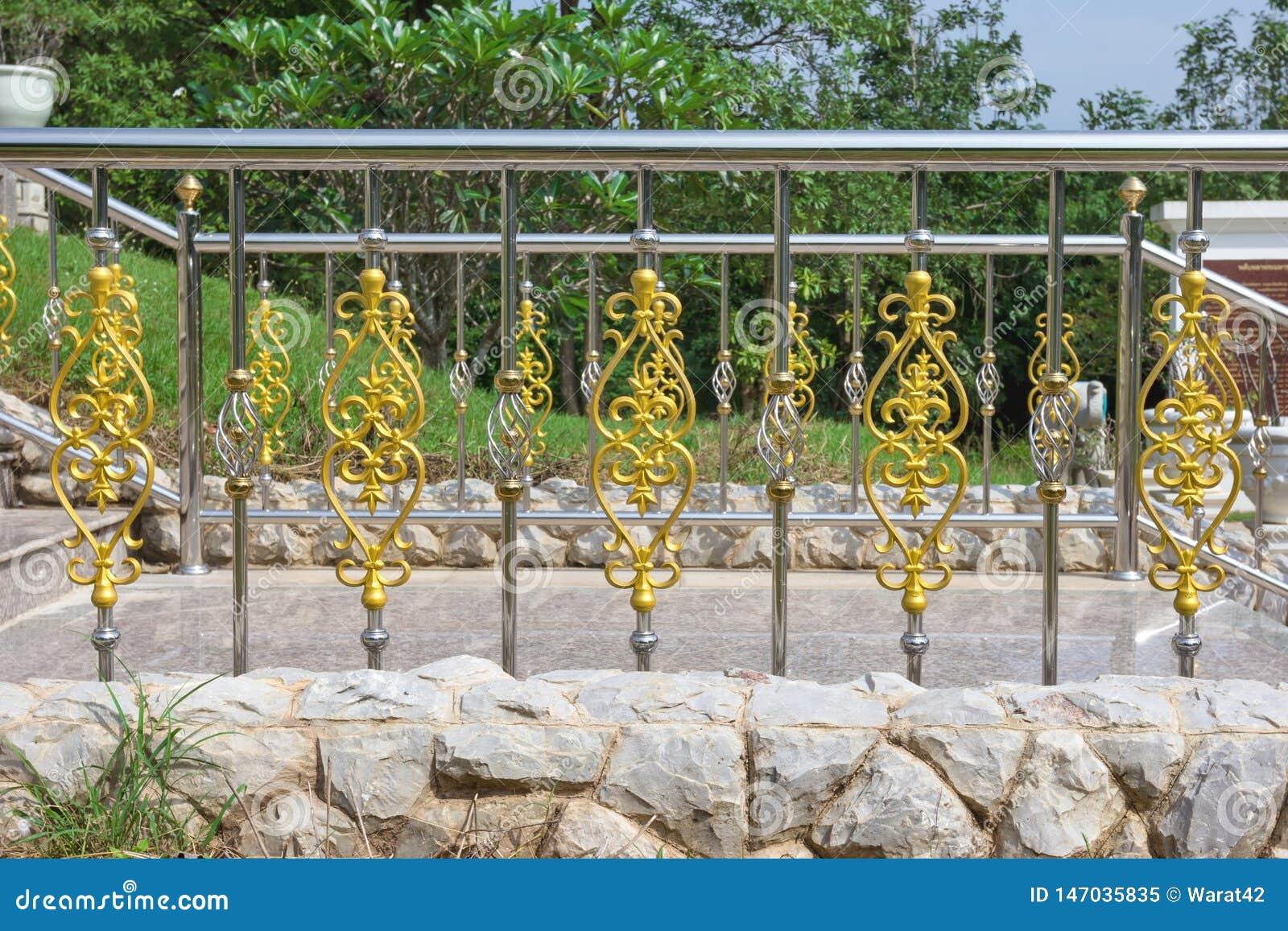 Rostfritt staket med prydnaden av guld