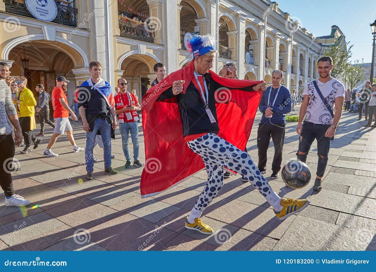 Rosyjski piłki nożnej fan z szalenie kapeluszem kopie piłkę, St Petersburg