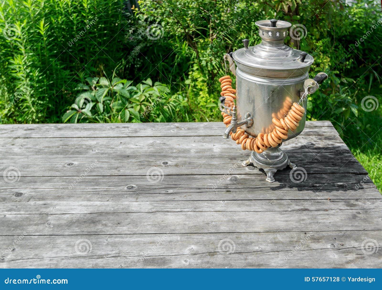 Rosyjski samowar na nieociosanym drewnianym stole z jagodami i kwiatami