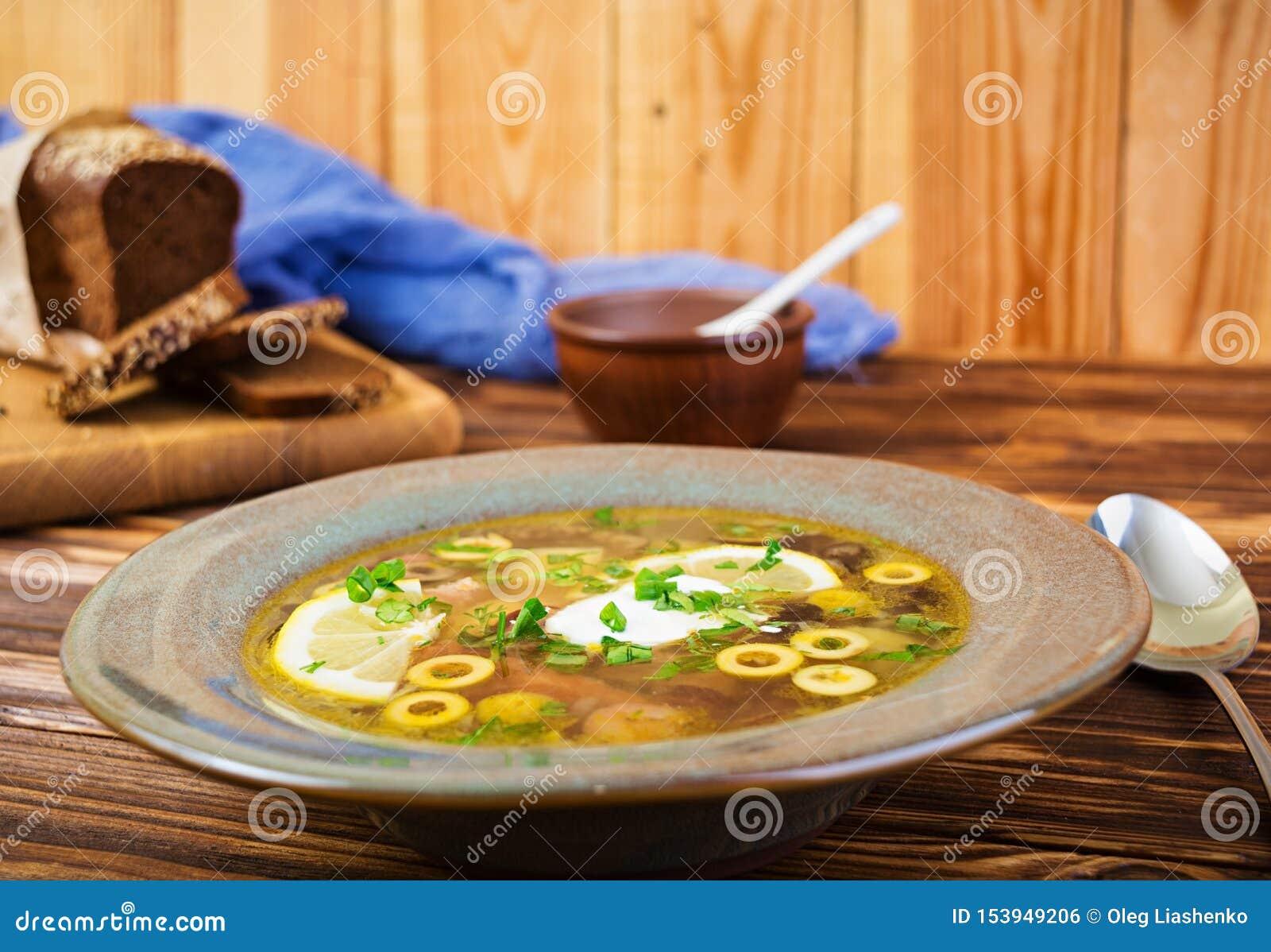 Rosyjski zupny Solyanka z kwaśną śmietanką na drewnianym tle