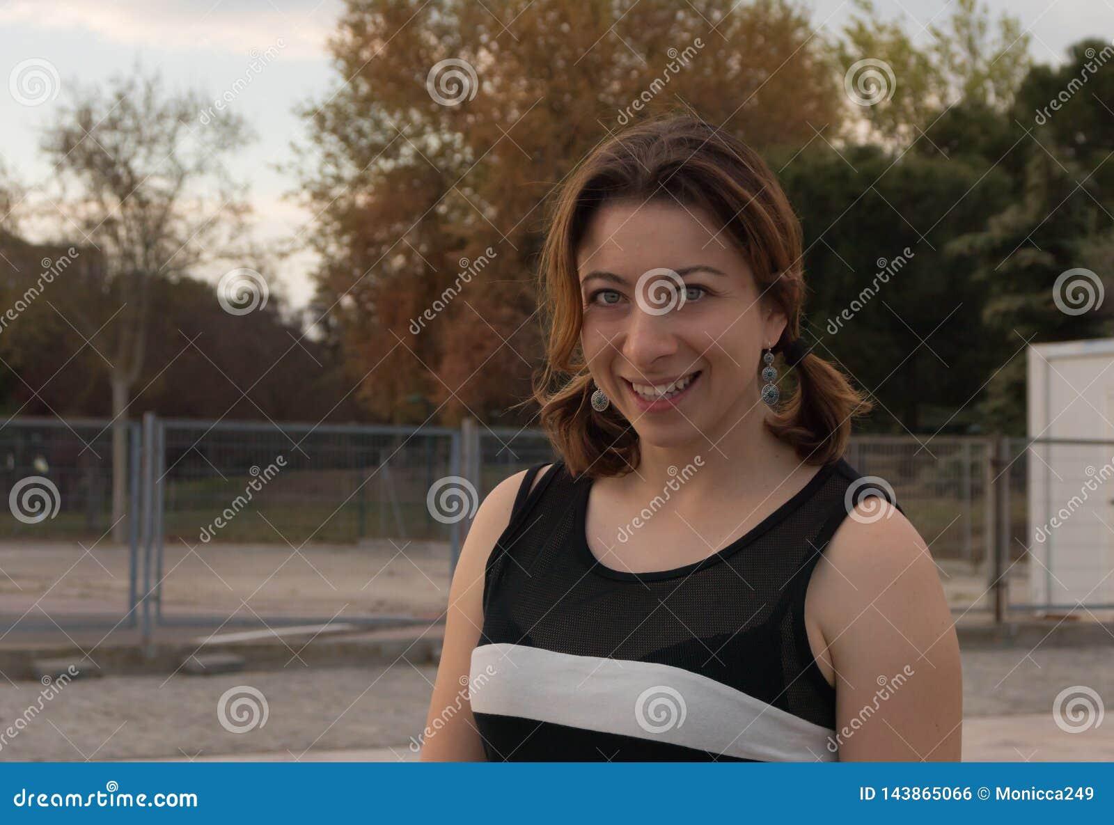 Rotäugige Frau mit grünen Augen lächelnd an der Kamera