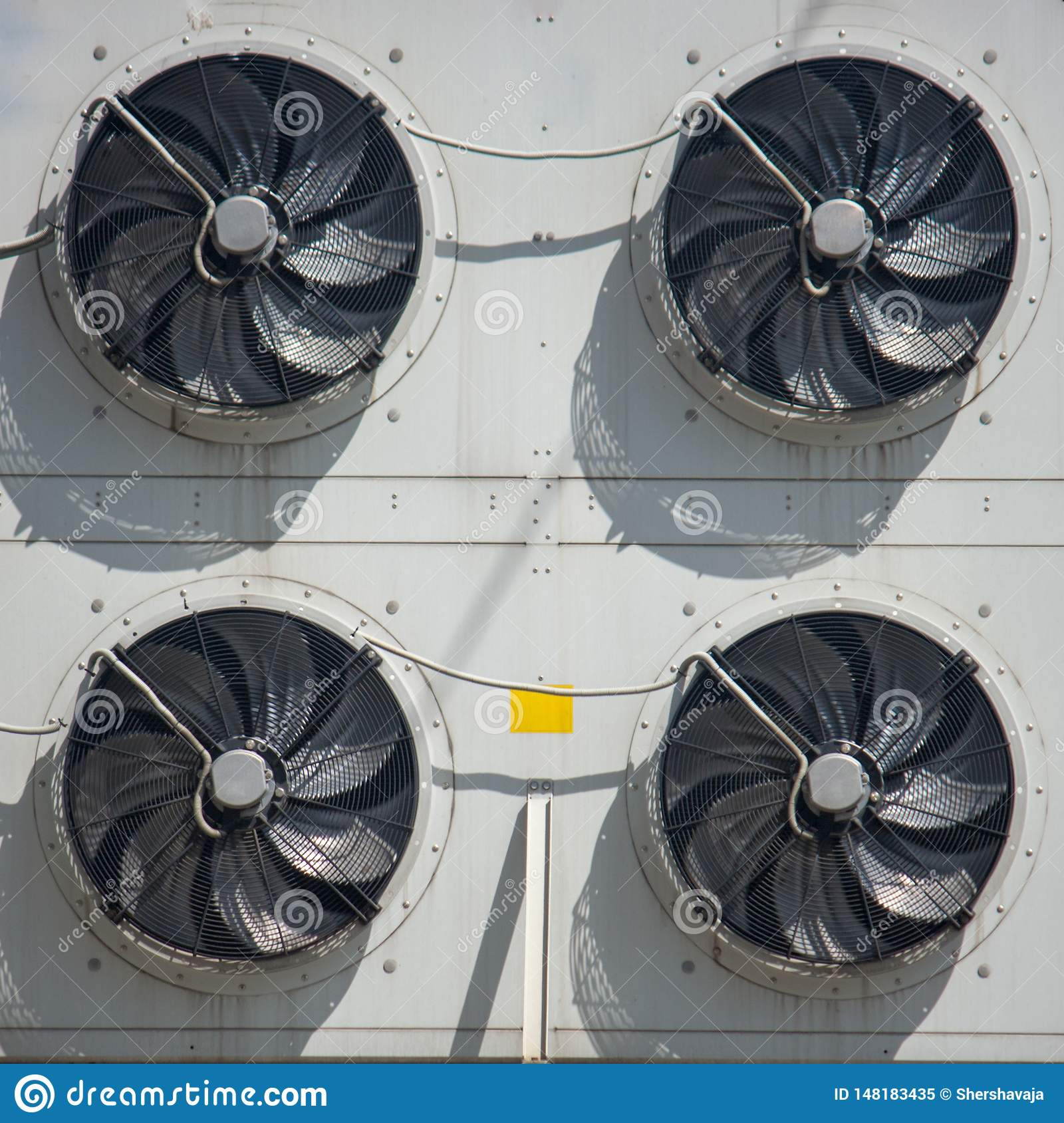 Rotating blades factory fan on the wall of the building