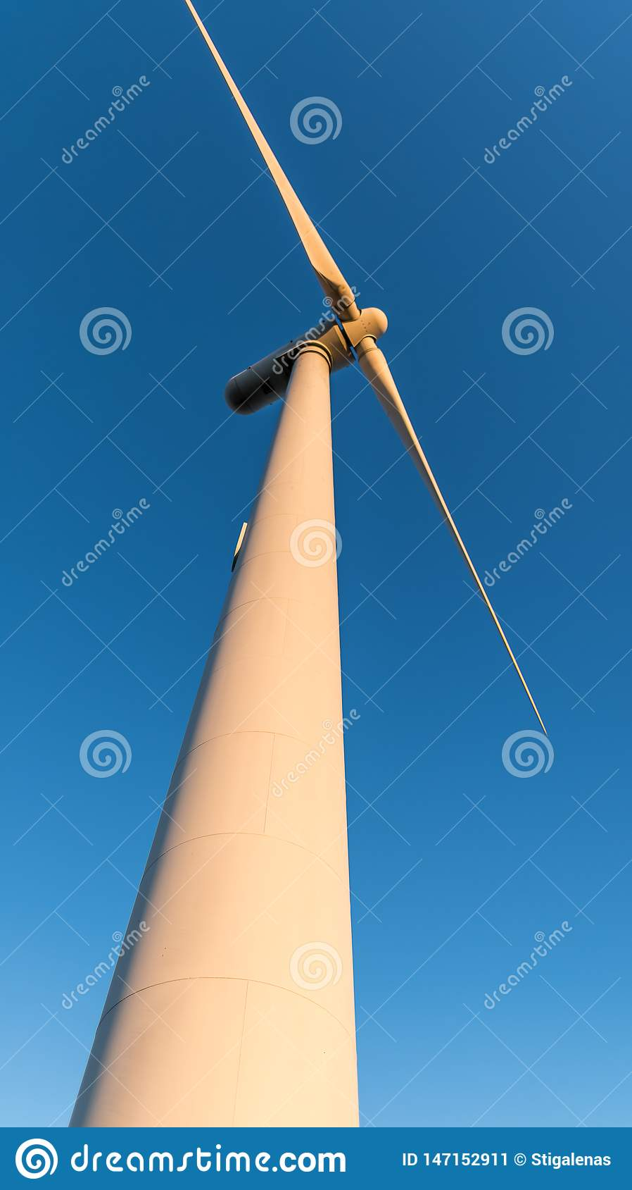 The rotating blades of a windmill against blue sky