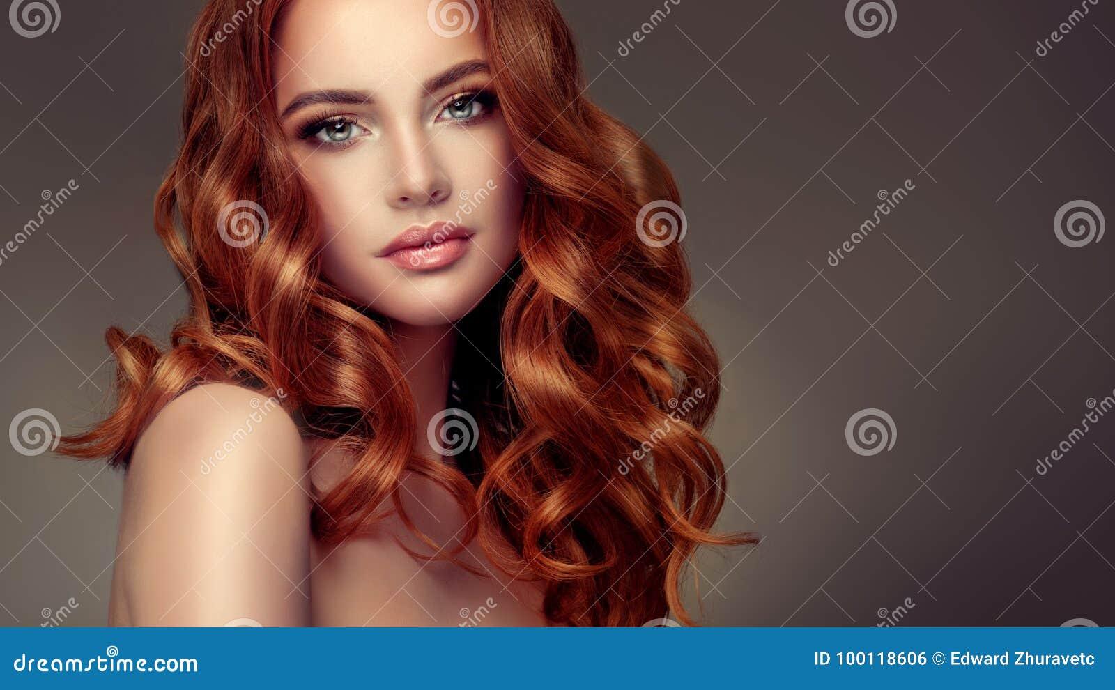 Rote behaarte Frau mit umfangreicher, glänzender und gelockter Frisur Attraktive junge Dame mit Kamm auf einem grauen Hintergrund