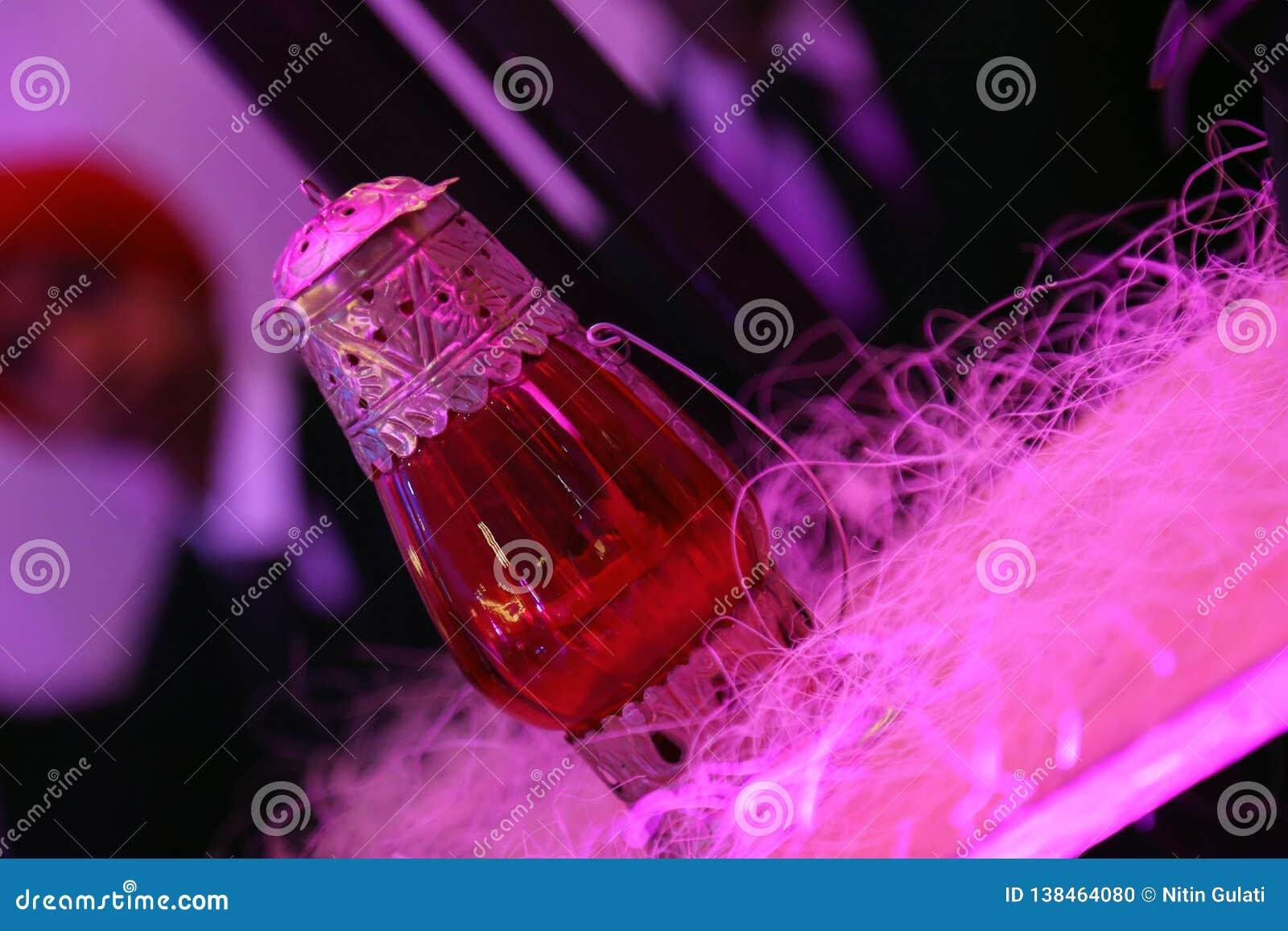 Rote Glaslampe mit der Metallarbeit lokalisiert mit Unschärfehintergrund