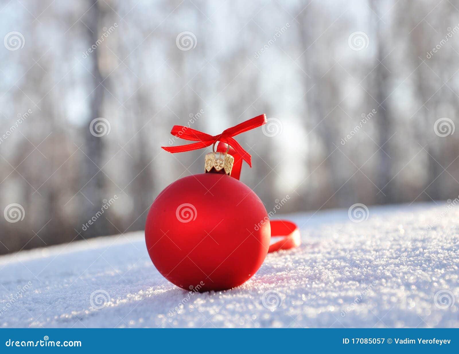 Rote Glasweihnachtskugeln auf Hintergrundschnee