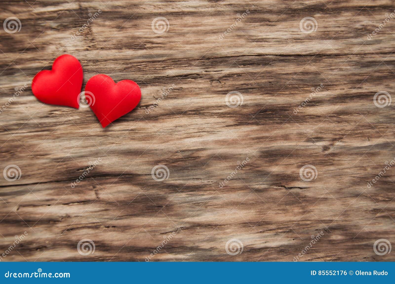 Rote Herzen auf einem hölzernen Hintergrund