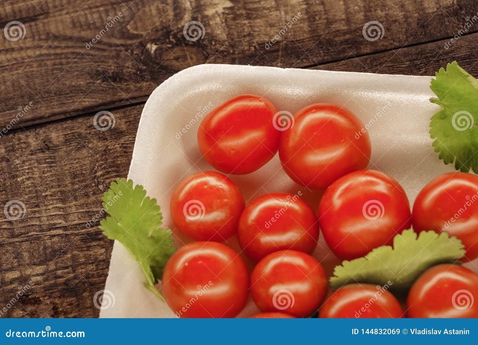Rote Kirschtomaten auf einer wei?en Platte mit einem h?lzernen Hintergrund
