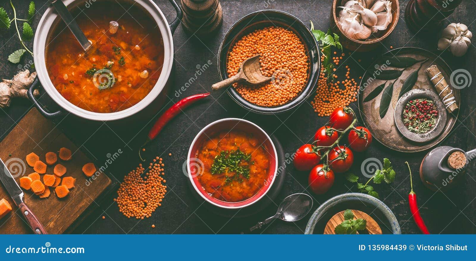 Rote Linsensuppe mit dem Kochen von Bestandteilen auf dunklem rustikalem Küchentischhintergrund, Draufsicht Gesundes Lebensmittel