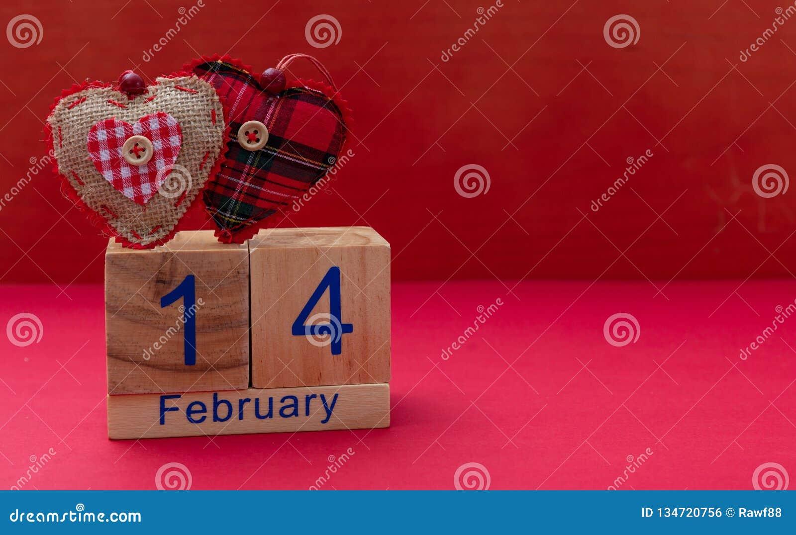 Rote Rose 14. Februar und zwei rote Gewebeherzen auf rotem Hintergrund