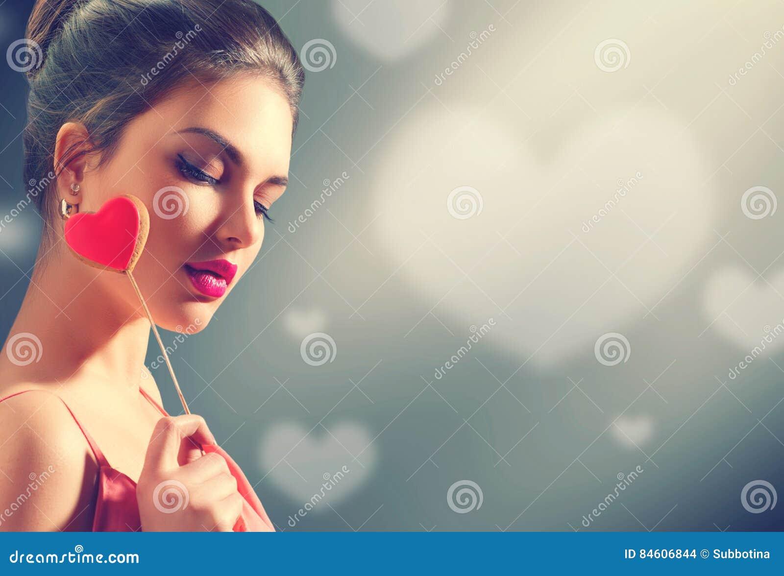 Rote Rose Junges vorbildliches Mädchen der Schönheit mit Valentinsgrußherzen formte Plätzchen