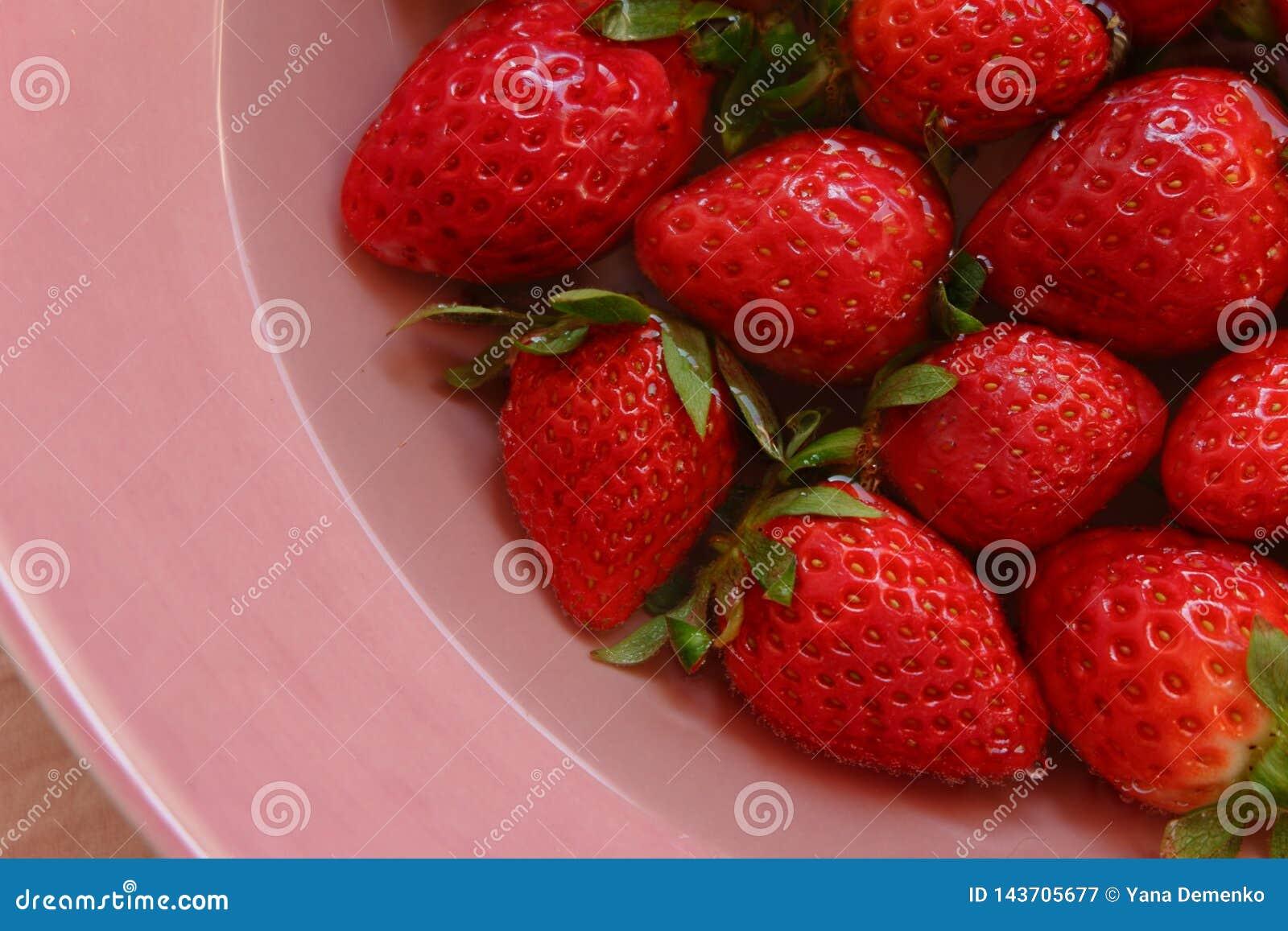 Rote strawberies der unterschiedlichen Größe auf der Platte