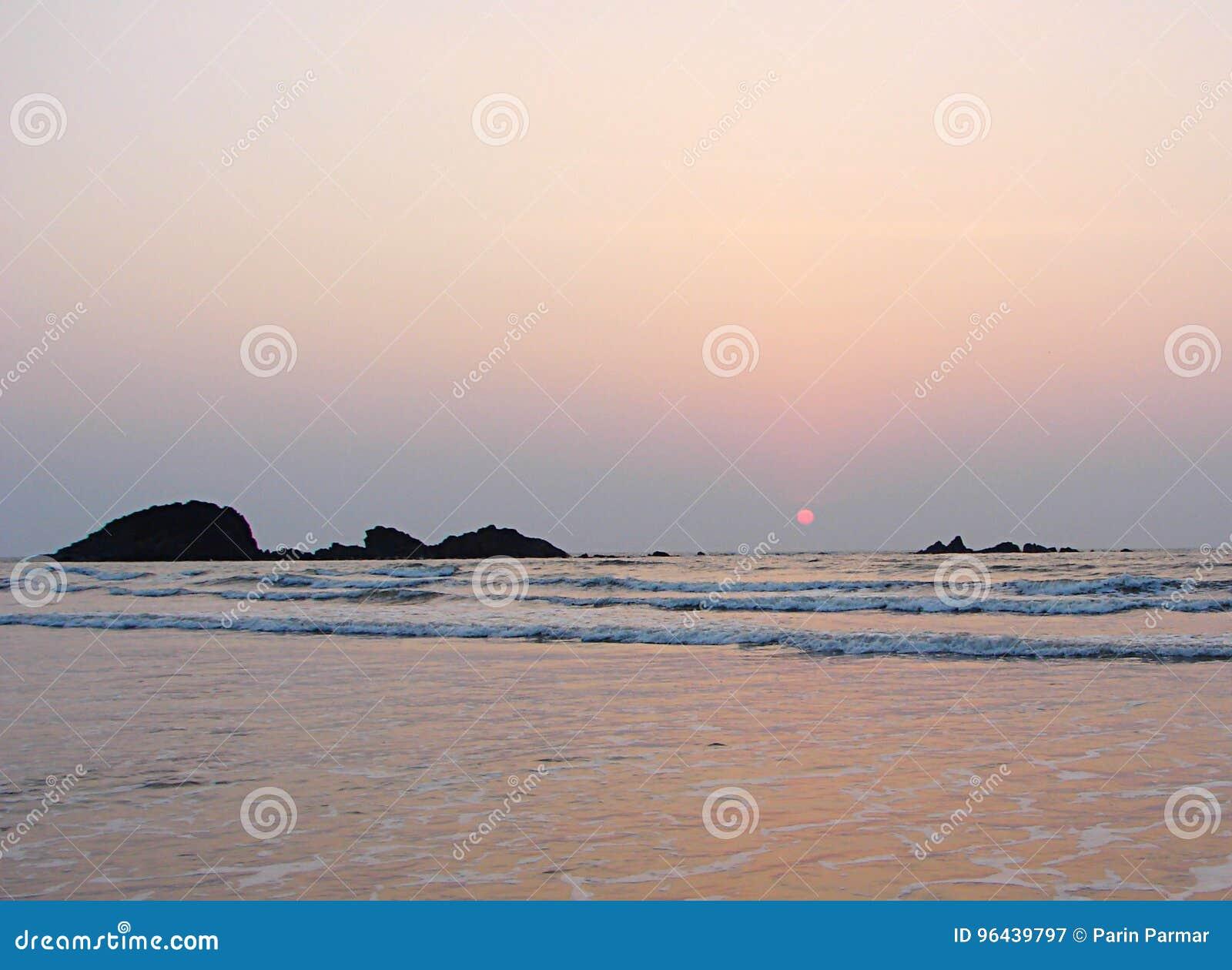 Rote Sun-Einstellung am Horizont über Meer am Muzhappilangad-Autokino-Strand, Kannur, Karala, Indien - natürlicher Hintergrund