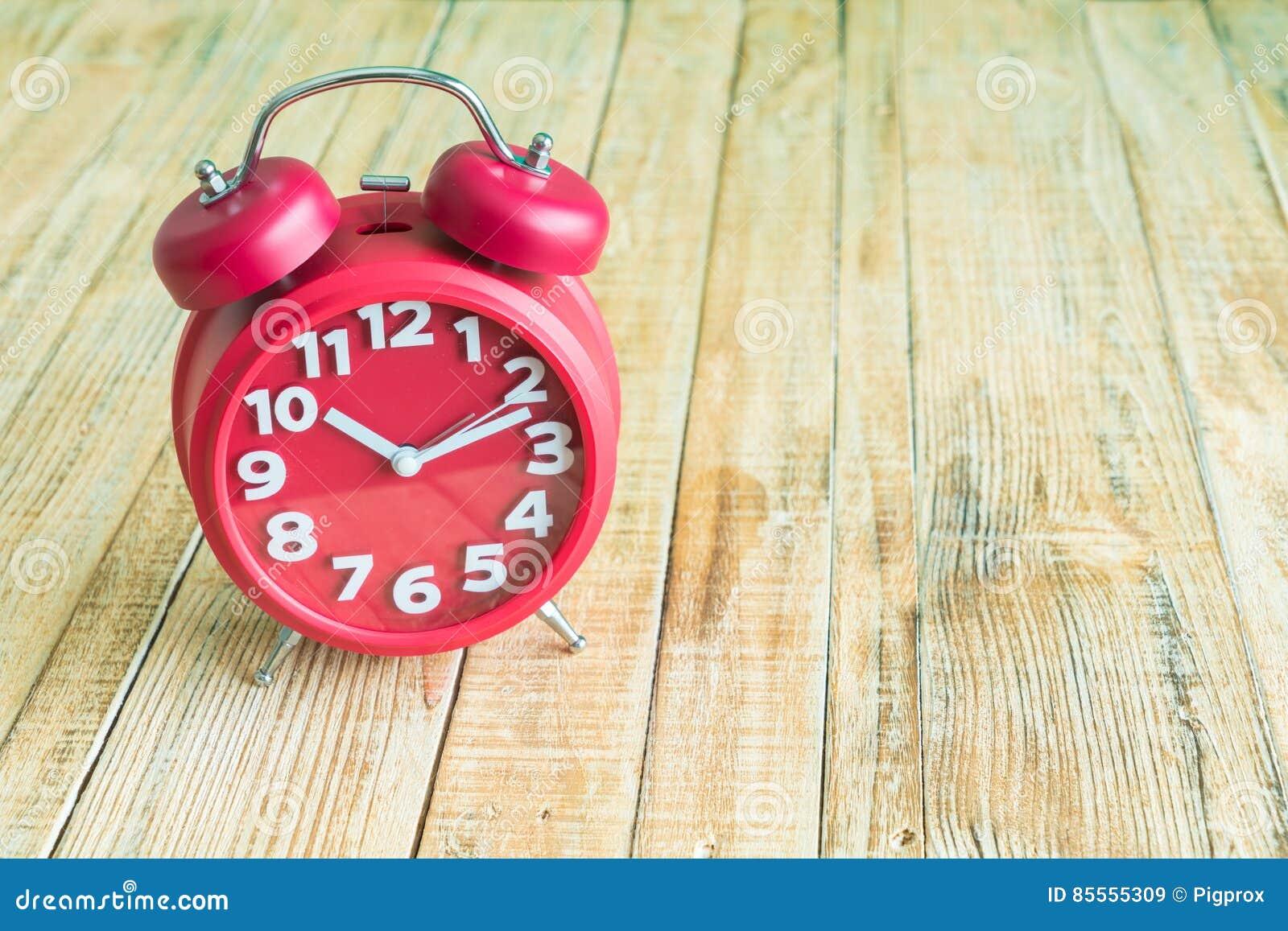 Rote Uhr auf hölzernem altem Hintergrund