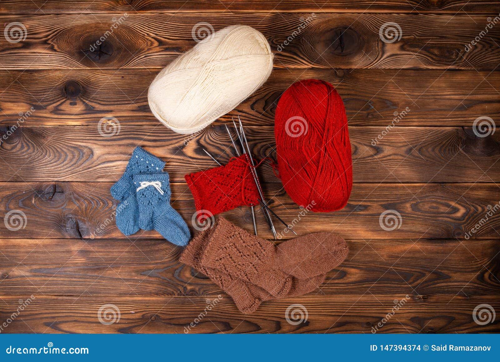 Rote und weiße farbige Bälle des Fadens, der Stricknadeln und der gestrickten Socken auf einem hölzernen Hintergrund
